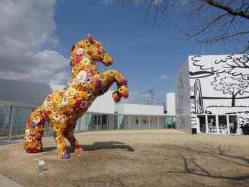 """チェ・ジョンファ作 フラワー・ホース  """"十和田現代美術館""""は現代美術を多く扱うアートスポット。馬とゆかりのある十和田の歴史を感じさせつつ、おもちゃ箱のような色使いや発想のユニークさにワクワクできます。 桜の名所としても有名な十和田市の大通り「駒街道」から見られる作品です。"""