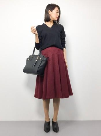 スカート以外はすべてブラックで揃えた秋仕様のレッドコーデです。ヘリンボーンツイードという素材感も秋らしく、深みのある色合いとぴったりとマッチしています。