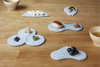 シンプルな石の豆プレートは、どれもどこかで見た懐かしい形ばかり。実はこちらは家紋をモチーフにした豆皿なんです。おうぎ、はなびら、ひょうたん、ねじり、まつなど、どのプレートも縁の丸みをとり薄く仕上げているので、石のお皿とは思えないほど、やわらかな印象で、とくに木目調のテーブルと相性がバッチリ。