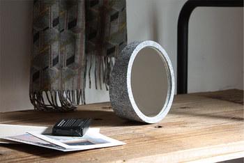 円形のフォルムが美しい置き型ミラー。底面の奥行きを広げることで重心が低くなり、しっかりと安定性が確保されています。それだけでなく、底面に奥行きがあるので、鏡面の裏に小物を収納しておくことができ、デザイン性だけでなく機能面もバッチリ。