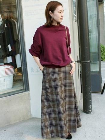 マキシスカートも動きに合わせてふわふわと動く、フレアタイプで個性を演出。秋のトレンドカラー、ボルドーのトップスと合わせて。