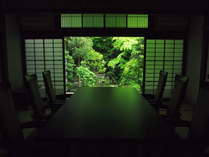 秩序のある美しい格子欄間・・・縁側から部屋へと光を通します。鴨居の上部には小さな格子戸の引き戸で開け閉めできる明かり取り欄間が。その下には、障子の引き戸が美しく開かれ、見事な調和を見せる伝統的な和室のしつらい。大きなテーブルと椅子がモダンな空間です。