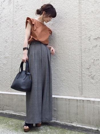 ストンとした落ち感のあるグレンチェックのハイウエストのワイドパンツに、デザイン性のある袖が素敵なテラコッタのトップスがオシャレ。小物は全てブラックレザーでまとめて統一感を。
