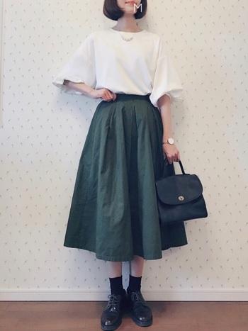 落ち着きのあるモスグリーンは、大人可愛いナチュラル女子にも取り入れやすいカラーです。ひざ下の長めミディアム丈のフレアスカートが上品で素敵。小物はすべて黒で統一、袖デザインにボリューム感のあるトップスを合わせてほんのりフェミニンに。
