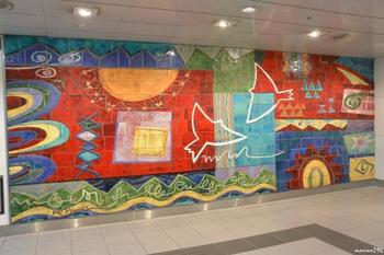 天津恵 作 Bright Time  渋谷マークシティといえば岡本太郎作の巨大壁画「明日への神話」。その前から銀座線乗り場に向かう階段を登り、突き当たりに見えてくるのがこちらの壁画。鮮やかな色彩と心地よいリズムの構成に「また明日も頑張ろう」と朗らかな気持ちになれる作品です。壁画横には作者の詩も。