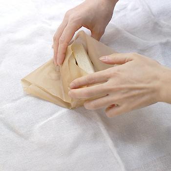 3.  向こう側の左右の端を三角形に畳みます。(四角い箱を包装紙で包む「キャラメル包み」のようなイメージ。)
