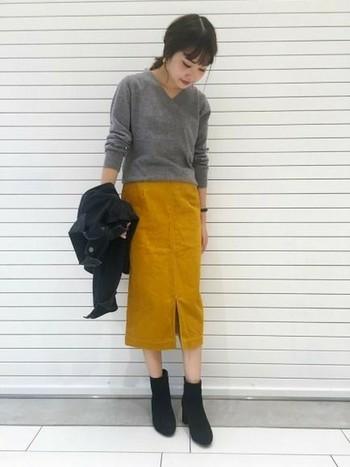 今年はタイトスカートやスリット入りのスカートも人気です。印象的なマスタードカラーのボトムスには、落ち着いたグレーニットで大人っぽく仕上げて。