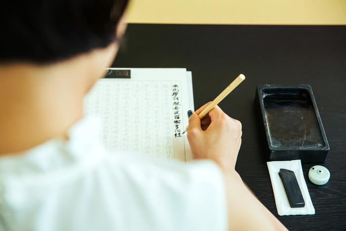 「写経」とは、その字が表す通り、「お経を写す」こと。透けて見えるお手本の文字をなぞるように写経するので、難しい漢字も簡単に書くことができます。