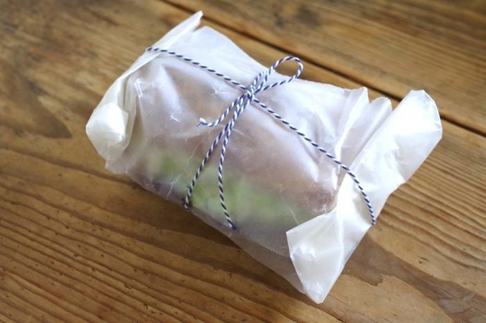 サンドイッチをワックスペーパーでくるんで。リボンやラフィアでくるりと結ぶだけで可愛いアクセントに。
