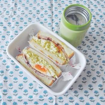 お弁当箱に詰める場合は、全体をラップで包んだサンドイッチをそのままカット。その後ワックスペーパーで補強すればきれいに盛りつけられます。