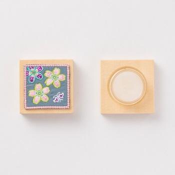 ヒバ木に刺繍のアップリケをあしらった中川政七商店の練り香水。香りは華やかなに香るサクラとスミレの二種類。ホホバ種子油やミツロウなど肌に優しい成分で作られているので、安心して使用できます。