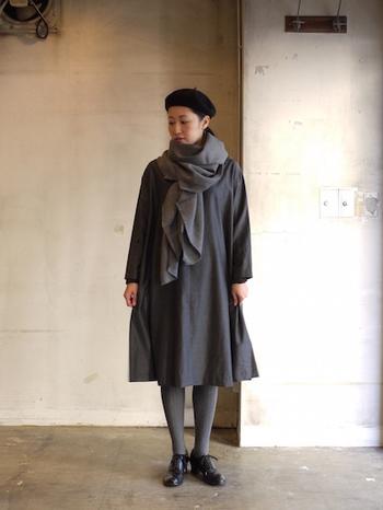 シンプルなデザインのバスクドレスのワンピースには、ボリュームのあるストールを合わせて個性的に。