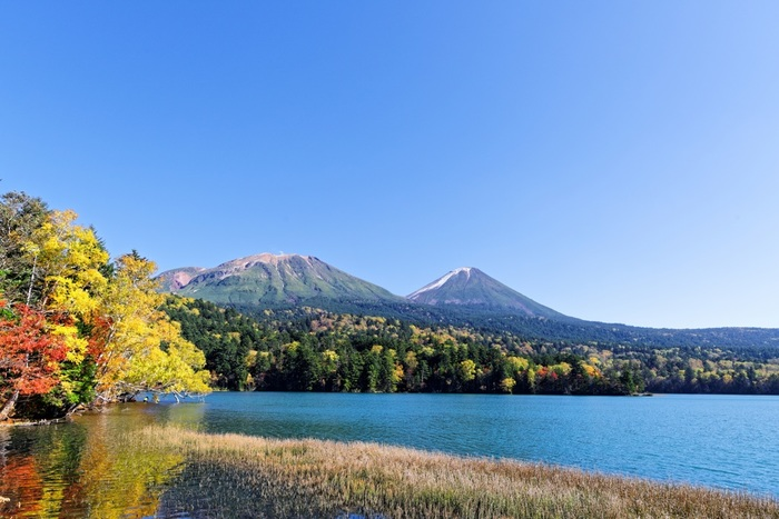 雄大な雌阿寒岳、雄阿寒岳を望む、足寄町(あしょろちょう)の「オンネトー」。季節や天候によって湖の色が違って見えることから別名「五色沼」とも呼ばれています。針葉樹と広葉樹が混じった紅葉は、緑と赤や黄色の色合いがはっきりとしていてとても鮮やかです。