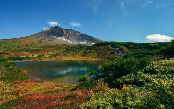 日本で一番早く紅葉が始まる、北海道の屋根「大雪山系旭岳」。早い場所では8月下旬から紅葉が始まり、9月上旬~中旬には見ごろを迎えます。9月中旬ごろには冠雪した旭岳と紅葉のコントラストが楽しめることもあり、とても美しい風景が見られます。