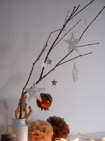 庭で拾った枯れ木の枝に、軽いオーナメントを吊るして。下からの灯りが息吹を吹き込みます。