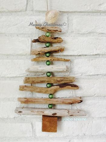 流木をビーズと紐で留めて作られたクリスマスツリー。緑のビーズと流木が上手くマッチしています。