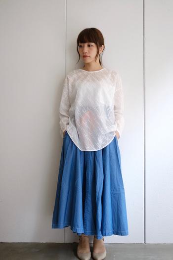 フレア感のあるデニムのロングスカートは、爽やかでありながら可愛らしい雰囲気。ほんのり透け感のあるトップスと合わせると、フェミニンさが引き立ちます。