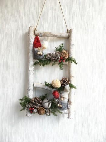 毛糸で編まれたほっこりサンタと、森の香りがするような松ぼっくりなどの組み合わせたクリスマス飾り。好きなパーツを集めて自分だけの壁掛けを作るのも素敵です。