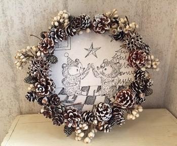 刺繍枠に麻生地を張り、イラストを描いています。クリスマスらしい絵を描くのもいいですね。周囲には、松ぼっくりやメタセコイヤなどをあしらって。