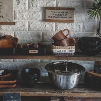 """木のシェルフに、ウッドプレートやコップ、バスケット、ステンレスのザルを並べた""""見せる収納""""。ナチュラルな天然素材の温もりとシルバーのスタイリッシュさが見事に調和したキッチンになっています。味わいのある渋さがかっこいいですね!"""