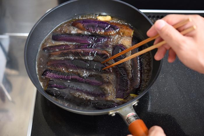 皮面が全体的にきれいな紫色になったら返し、残りの面も軽く焼き、出汁やしょうゆなどで合わせた調味料を加えます。ぐつぐつと3分ほど煮たら、保存容器に煮汁ごと移しておきましょう。