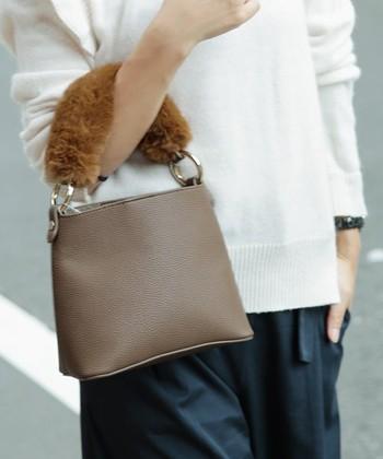 持ち手にふわふわのファーをまとったきれいめのハンドバッグ。白や茶系が多いファーだからこそ、ブラウンベージュのバッグとよく馴染んでくれますよ。