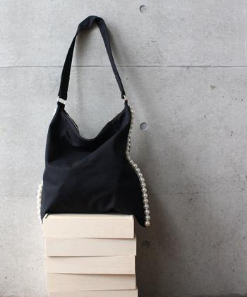 サイドがパールで縁取りされた合皮のバッグ。たっぷり容量の大きめサイズで、お仕事用のサブバッグとしても◎斜め掛け出来るカジュアルバッグだけど、サイドのパールによって女性らしさもプラスできます。