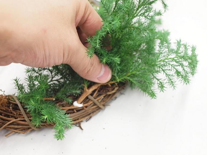 2.5~7cm程度に切ったヒムロスギの枝先に木工用ボンドを塗り、ベースのツルの間に差し込み、固定します。バランスを見ながら、ベースの表側全体に配置します。さらに、ヒバの葉をポイントになるように差し込んでいきましょう。