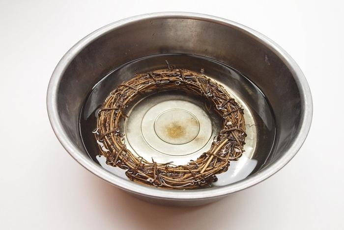 【手順】 1. サンキライで作ったリーフベースを水に浸けます。水を含んで柔らかくなったら、ツルとツルの間隔を広げ、花を差し込みやすくなるよう形を整えます。