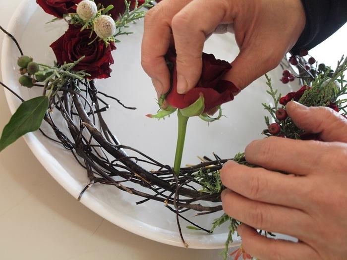 2.平らな水盤の上に浮かせた状態で作っていきます。まずは短くカットしたバラを、茎が水に浸かる位置にまでしっかりと差し込みます。同じように他の花や果物、ヒムロスギなどの針葉樹も差し込んでいきましょう。ぐるっと一周、生けていきます。
