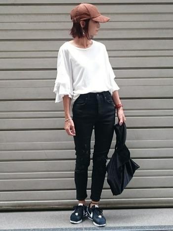 濃いブラックスキニーに、ふわっとした裾デザインがトレンド感たっぷりの白トップスを合わせ、クールになりすぎないようにまとめています。キャップのさし色も効いてます!