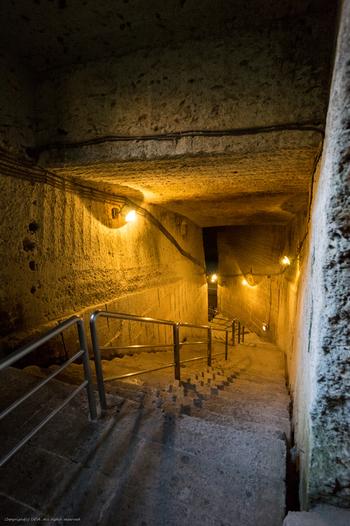 広さ2万㎡、深さ30mを超える巨大空間への階段。まるで異世界への入口を思わせる、神秘的な雰囲気が漂います。  階段を下りていくほどに、外気とは違う冷たい空気が、肌に感じられます。