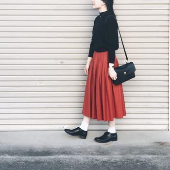 黒のハイネックニットに赤のプリーツスカート。小物も黒で揃えて大人っぽくまとめたところに白の靴下を合わせれば、力の抜けた優しいコーデに。