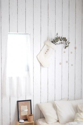 雪の結晶のシールと白いクリスマスの靴下で、真っ白な壁を冬らしい雰囲気にデコレーション。