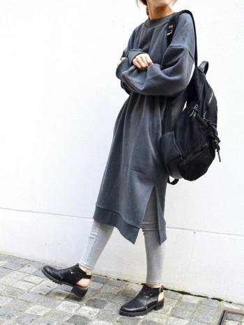 青みがかったグレーのスウェットワンピースにグレーのレギンス、肩からラフに掛けた黒リュックと靴でシックにまとめた大人のリラックスコーデです。