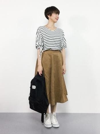 ボーダートップスにベージュのフレアスカートを合わせた、シンプル&ベーシックなスカートスタイル。背負うのではなく、こんな風に取っ手の部分を持つスタイルも新鮮です。