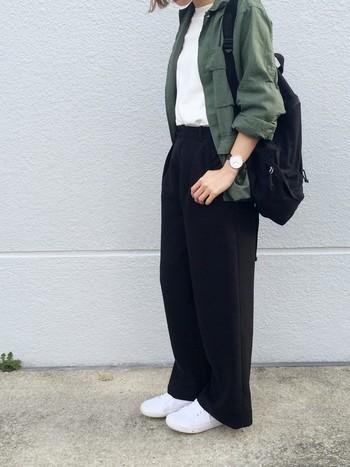 カーキのジャケットに黒のパンツと黒のリュックを合わせ、インナーと靴は白でまとめたミニマルなコーディネート。