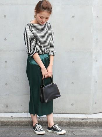 タイトなシルエットのサテンスカートは、より女性らしい印象に。こっくりとしたグリーンが華やかです。