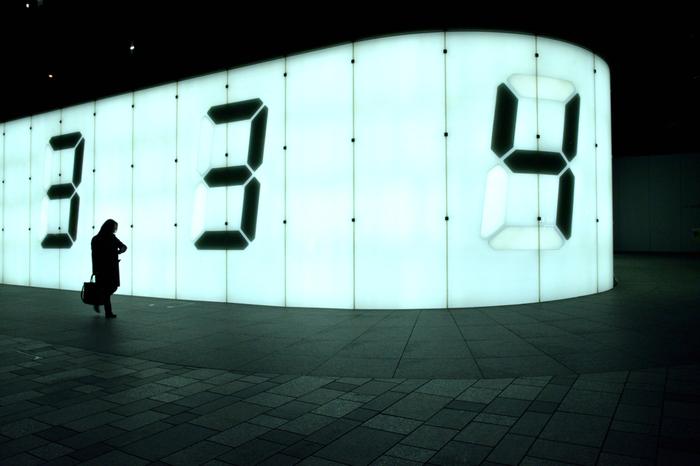 """宮島達男 作 Counter Void -光の壁-  2003年に六本木に設置された作品。巨大な発光する壁をバックに、それぞれの速度で数字がカウントダウンされます。3.11 東日本大震災後、犠牲者への哀悼の意を表すため消灯されていましたが、生と死を一人一人に問いかける試みとして2016年から3月の3日間のみ点灯するイベント""""Relight Days""""が開催されています。  街角で淡々と数字を刻む巨大な壁は、私たちに今を生きるイマジネーションを与えてくれます。"""