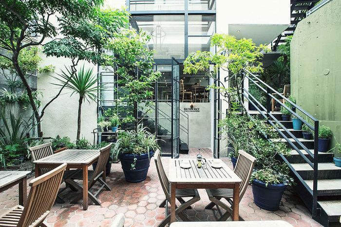緑いっぱいの中庭を中心に建つのは、2階建てのお店。木を基調とした広い店内も心地よいですが、天気の良い日はテラス席も居心地バツグンです。