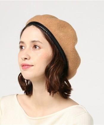 縁にトリミングがあるベレー帽を、後頭部をふわりと包む感じでかぶったスタイル。表情も明るく見え、フェミニンな服とも相性ぴったり。