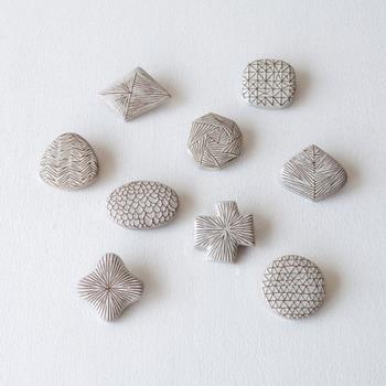 繊細な手描きの線が織りなす複雑なパターン模様のブローチは、小石のようなぷっくりとした肉厚感と、釉薬のやさしい艶が素敵。