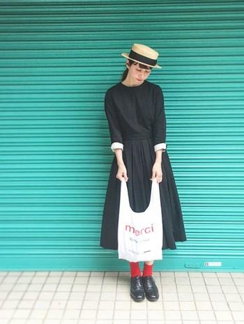 シンプルで女性らしいラインの黒のワンピースは袖を折り返したときに見える白がポイント。赤の靴下を挿し色に、赤文字入りの白のエコバッグでバランスのいい白・黒・赤、3色コーディネートの完成です。