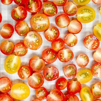 半分に切ったトマトをオーブンの天板に並べ、塩を振ります。クッキングシートを敷いた上にまんべんなく並べて下さい。
