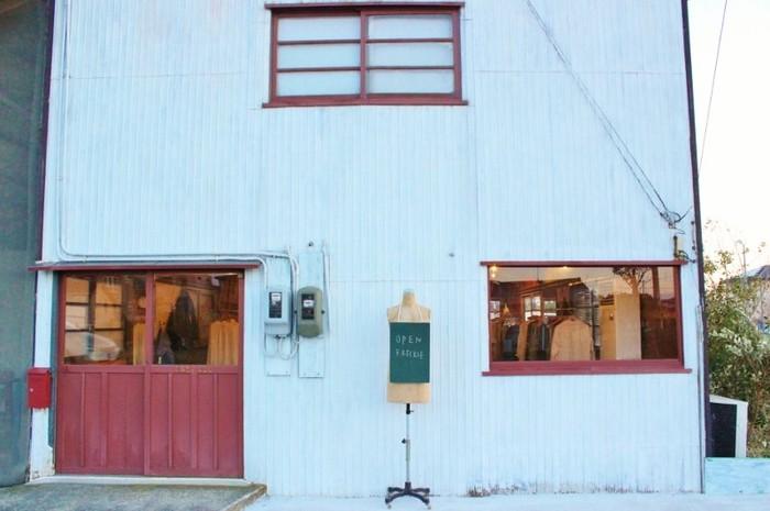 自然豊かな場所にあるアトリエ兼ショップ。白い壁と赤い入り口が目印です。