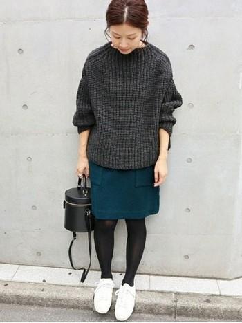シックなGREEN(グリーン)のコンパクトなスカートには、落ち着いたトーンの杢色のオーバーサイズのニットを持ってくると、とてもバランスの良い着こなしができます。