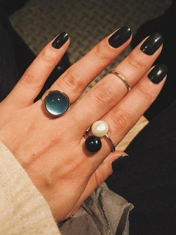 ハードな印象のブラックカラーも、白いニットと合わせるとシックな印象に。重ね付けしたリングで華やかさをプラス。