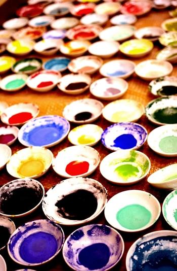 日本画には油絵やアクリル絵の具と比較するとずっと手間がかかる、扱いの難しい画材を使用します。  日本画の絵の具は色の元である顔料に、岩絵具という名前の通り、鉱石などを混ぜた絵の具を使います。瑠璃など宝石と同じ材料も使われているため、もともと高価なものでした。岩絵の具を溶かすのは膠(にかわ)という天然材料で、これと混ぜてペースト状にして描きます。