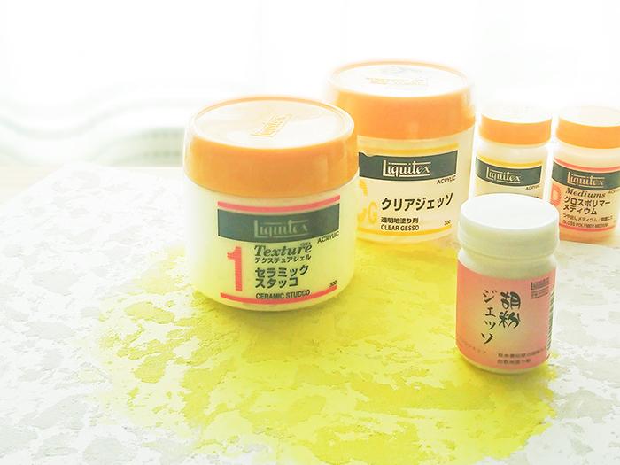 """色の元である顔料と、それをつなぎとめる接着剤が合わせたものが、一般的に使われている絵の具の中身です。 アクリル絵具は顔料と樹脂メディウムから出来ています。 この接着剤のことをメディウムと言い、そもそもは絵の具の構成要素のことを指していました。現在画材屋さんなどで売られている代表的なメディウムはアクリル絵の具のメディウムになります。  下地によく用いられるジェッソ、透明感を演出したり、波とか水しぶきの表現を作るグロスポリマーメディウム、ゴツゴツとした質感を作れるセラミックスタッコなどが様々な特徴を備えたメディウムがあります。面白いメディウムとしては、胡粉(※)の質感を再現した胡粉ジェッソや、乾きを遅らせるリターディングメディウムなどもあります。  作品に合わせてメディウムを活用すると制作の幅が広がります。写真(この記事のために著者撮影)は、セラミックスタッコを薄く塗って下地を作ってからイエローで着彩したイラストボードです。  (※)胡粉とは貝殻からつくられる日本画の白色絵具のこと。最近では""""胡粉ネイル""""で知名度を上げていますね。"""