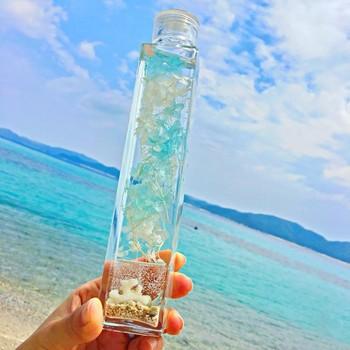 ガラスの中に、南国の浜辺と青い空を再現した、リゾート感たっぷりの作品。瓶の底の砂やサンゴ、貝殻は、ジェルで固めているので、浮き上がることはありません。空の部分は、ライトブルーと白のあじさいで、ゆれると雲のよう。キャップの部分も透明なボトルで、天に抜けるような開放感もすてき!